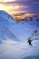 Rear view of skier moving down slope at sunset
