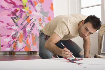 Young man painting on canvas on studio floor