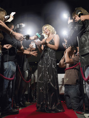 Young woman signing autographs on red carpet surrounded by paparazzi