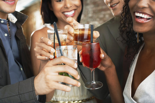 Closeup of happy multiethnic couples toasting drinks at the bar