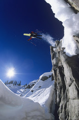 Low angle view of skier jumping from mountain cliff with blue sky in background