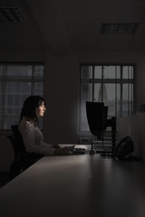 Side view of young businesswoman working on computer at night in dark office