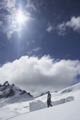 Side view of a mountain climber standing on snowy slope against clouds and sun