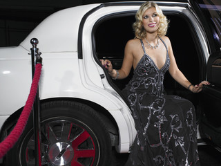 Beautiful young woman in evening wear getting out of limousine