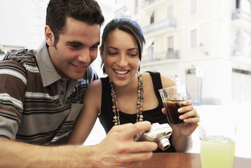 Happy young couple looking photographs on digital camera together while having drinks at sidewalk cafe