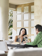 Romantic young couple enjoying wine at outdoor restaurant