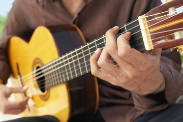 Midsection closeup of man playing acoustic guitar