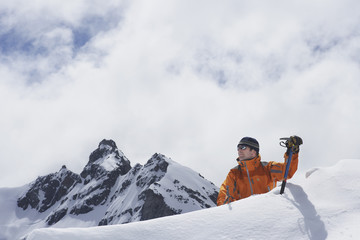 Male mountain climber reaching snowy peak against mountains and clouds