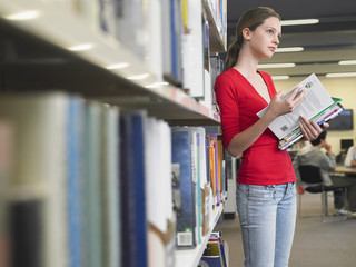 Thoughtful teenage girl reading books by shelves in library