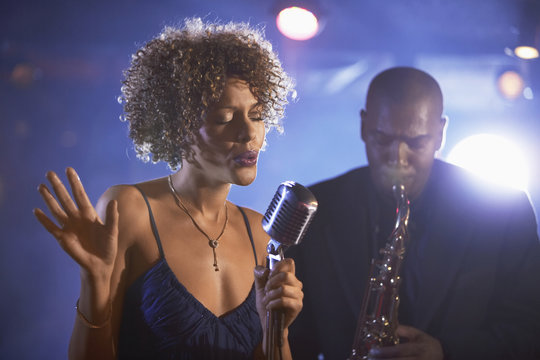 Female singer and saxophonist performing at the jazz club