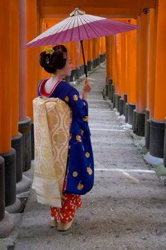 Portrait of a geisha holding an ornate umbrella at Fushimi-Inari Taisha shrine, which is lined with hundreds of red torii gates, Kyoto, Kansai region, Honshu, Japan