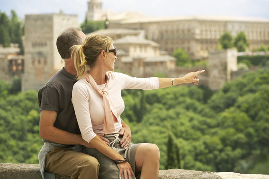 Middle aged couple sitting on wall with woman pointing at view, Granada Spain
