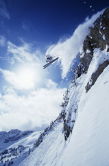 Low angle view of skier jumping from mountain against cloudy sky
