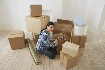 Portrait of smiling young woman unpacking moving box in new home