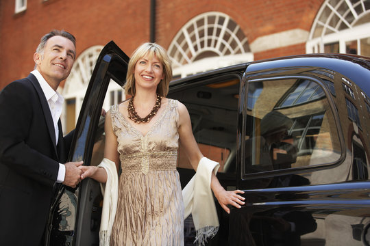 Happy well dressed couple exiting London taxi