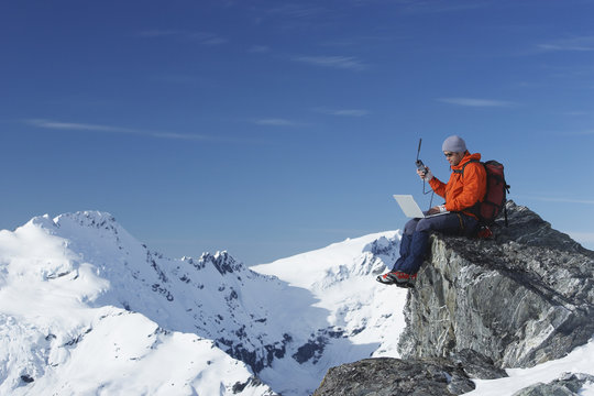 Mountain climber using laptop with walkie talkie on mountain peak against blue sky