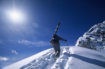Rear view of skier hiking to mountain summit against sky
