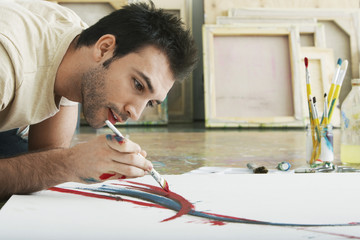 Closeup of a young man painting on canvas on studio floor