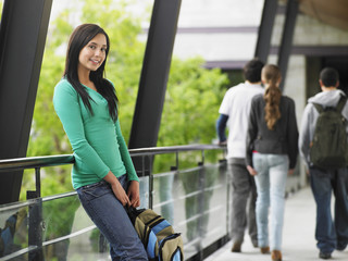 Portrait of beautiful teenage girl leaning against railing in university corridor