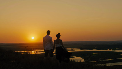 loving couple - brave young man and beautiful girl stands on high hill  looking to sunset silhouette, slider shot