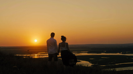 loving couple - brave young man and beautiful girl stands on high hill  looking to sunset silhouette
