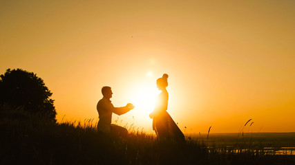 Romantic Silhouette of Man Getting Down on his Knee and Proposing to Woman high hill - Couple Gets Engaged at Sunset - Putting Ring Girl's Finger