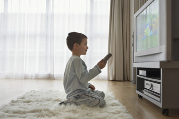 Side view of a boy sitting on floor and watching cartoons in television