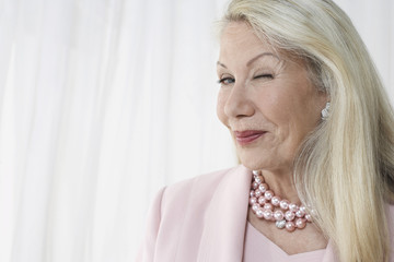 Closeup of a happy and glamorous senior woman winking against white background