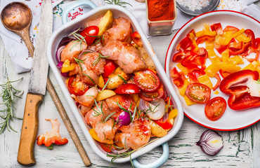 Chicken pieces with cut vegetables and red paprika powder in casserole , on light rustic background with cooking spoon and kitchen knife, top view