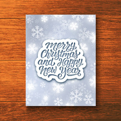 Merry Christmas and Happy New Year hand lettering text on white paper label over glowing winter background. Vector greeting card template with typography for holidays above wooden backdrop.