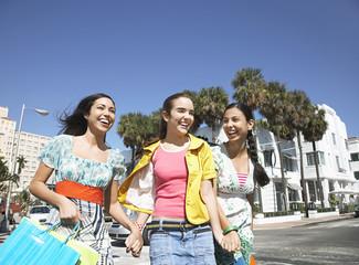 Cheerful teenage girls with shopping bags walking on street