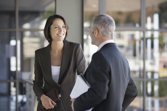 Happy businesswoman and businessman talking in office