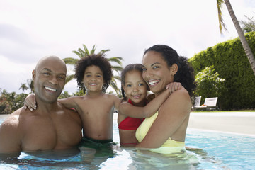 Portrait of happy African American parents with children in swimming pool