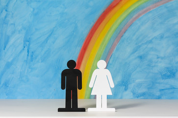 Man and women icons with a rainbow and blue sky to illustrate the concept of gender equality; medium shot for copy space.
