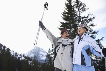Cheerful skiing couple in warm clothing with skis against mountains