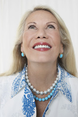 Closeup of a smiling senior woman looking up against white background