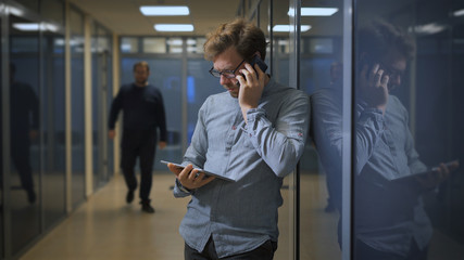 Young bearded guy talking on the phone while using tablet
