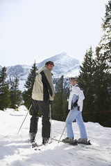 Rear view portrait of a skiing couple standing on ski slope