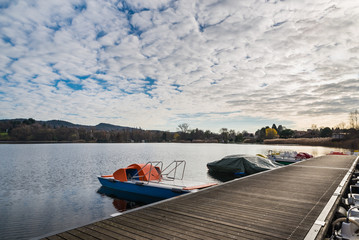 Panorama of Lake Monate with a sky with stratocumulus, in the foreground a wooden floating dock with pedal boats