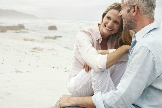 Happy loving couple sitting on beach