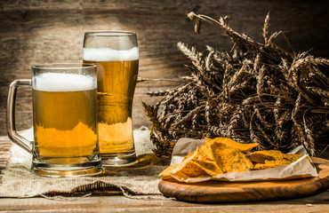 Beer in mug, glass with wheat spikelets and chips