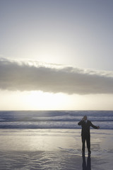 Middle aged businessman using cell phone in sea at sunset