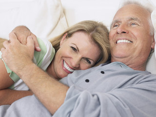 Closeup of a happy middle aged couple embracing in bed