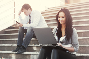 Young business man and woman with laptop on the steps