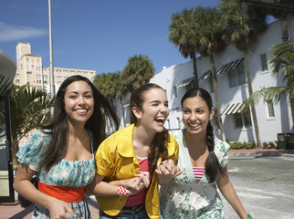 Cheerful three teenage girls with shopping bags crossing street