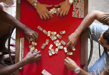 Overhead view of four people playing dominoes on a red table