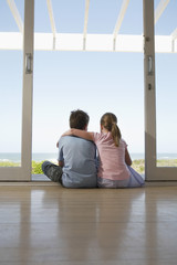 Rear view of young girl and boy sitting in doorway looking at view