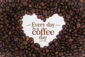 """Background made of coffee beans in a heart shape with message """"Every day is a coffee day"""""""