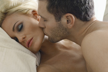 Closeup of a young man kissing woman's cheek in bed
