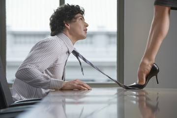 Side view of a highheeld businesswoman stepping on businessman's tie on desk